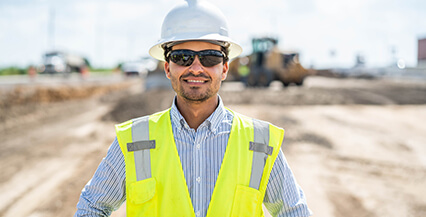 Man on a construction site that uses HCSS software